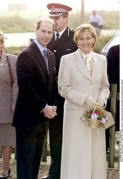 2002 : Sophie de Wessex et son époux, le prince Edward lors de l'inauguration d'une nurserie dans le Norfolk. Elle porte un long manteau beige en coupe droite ainsi qu'un petit sac panier. Un style élégant et chic.