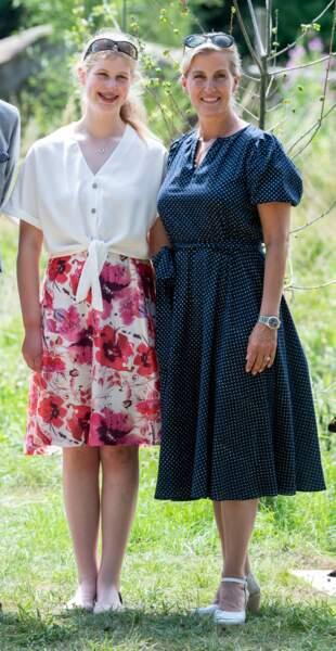 """23 juillet 2019 : Sophie de Wessex est en compagnie de sa fille, Louise, 16 ans. Elles visitent le zoo """" Wild Place Project """" à Bristol. Elle porte une petite robe à pois bleu marine ceinturée au niveau de la taille. Pour une fois, elle ne porte pas de chapeau, remplacé par une paire de lunettes de soleil."""