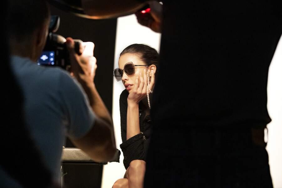 Margaret Qualley porte un modèle de lunettes de soleil papillon doté d'un collier de perles blanches.