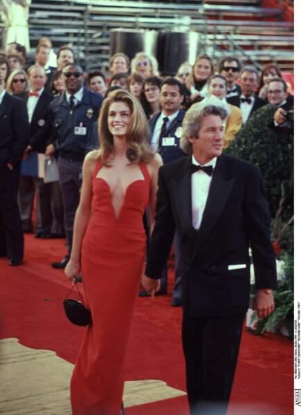 Cindy Crawford est accompagnée de Richard Gere lors de la cérémonie des Oscars en 1991. Elle porte une sublime robe rouge au décolleté plongeant et structuré de la maison Versace