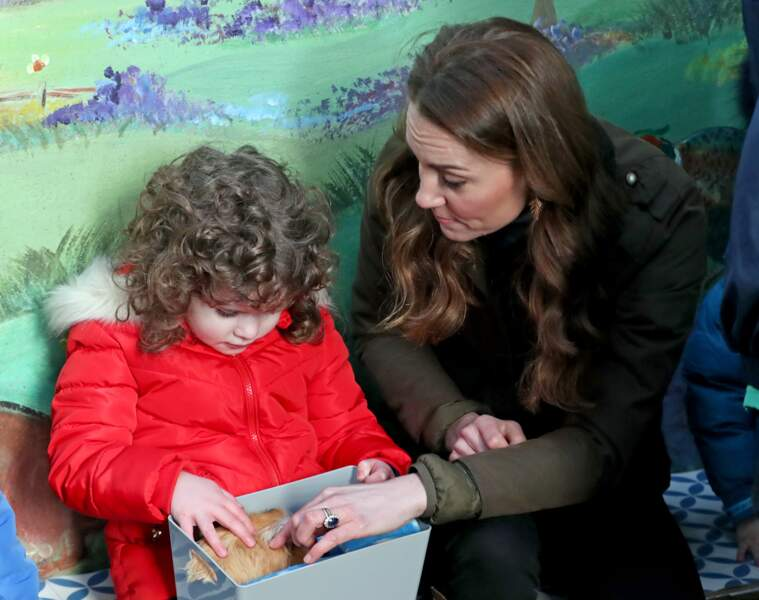 Kate Middleton en pleine intéraction avec une fillette fascinée par un cochon d'inde : la duchesse croit beaucoup à la force des liens sociaux dans l'épanouissement d'un enfant.