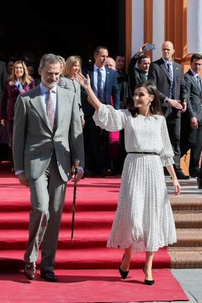 Le roi Felipe VI d'Espagne et la reine Letizia saluent la foule lors de la visite d'une église à Huelva le 14 février 2020. Cette robe blanche à pois est un modèle que la reine apprécie particulièrement. Elle portait une robe similaire lors d'une apparition à Séville début février 2020