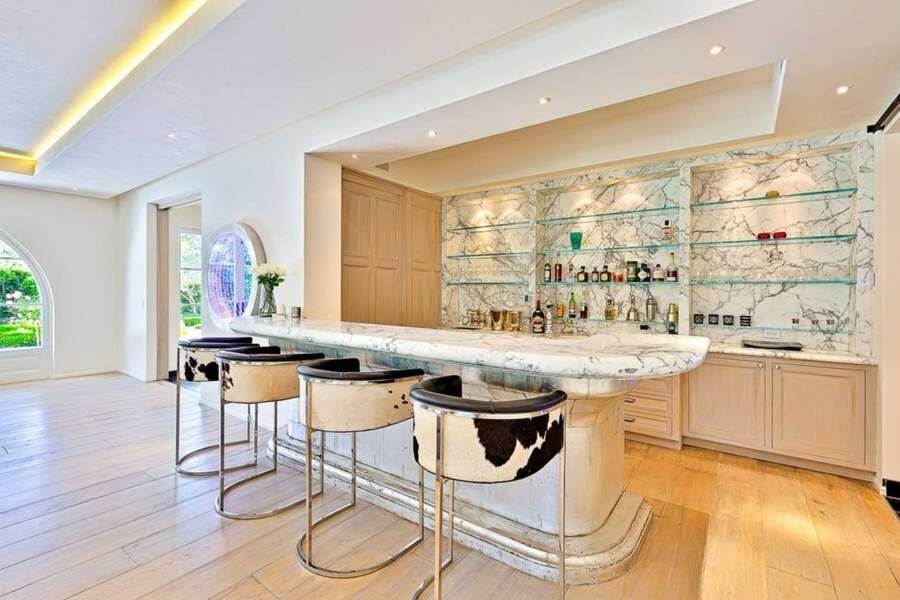 Un bar moderne a été installé avec un comptoir en marbre, des tabourets et des skakers pour préparer des cocktails à volonté