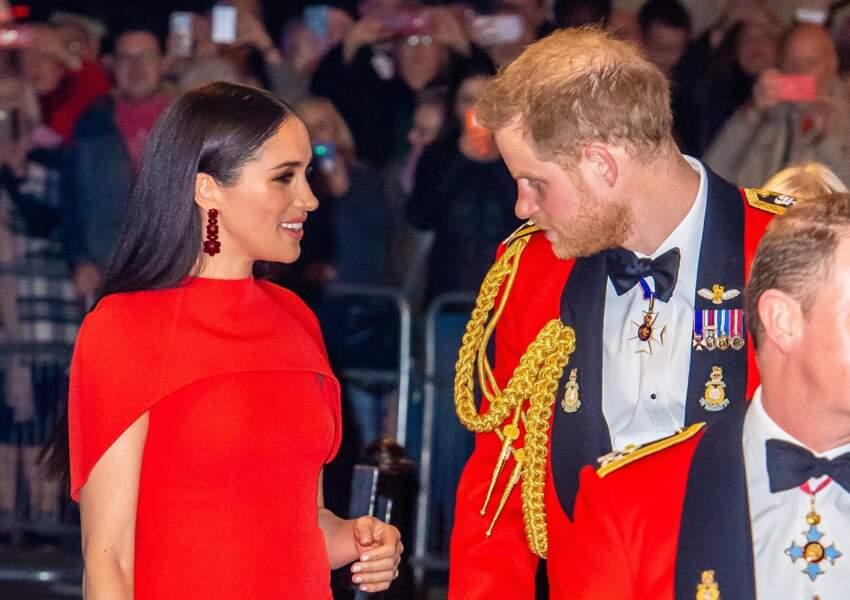 Le prince Harry admire Meghan Markle, son épouse, sublime dans sa robe-cape rouge Safiyaa et son brushing lisse parfait.