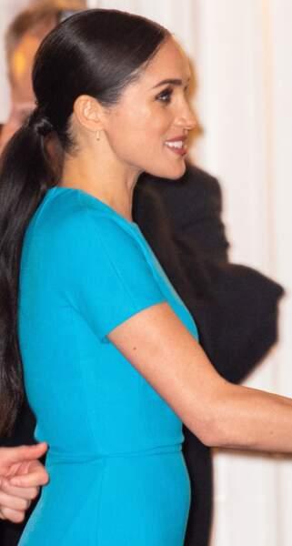Meghan Markle stylée avec une queue-de-cheval basse dont l'attache est une mèche de cheveux enroulée.