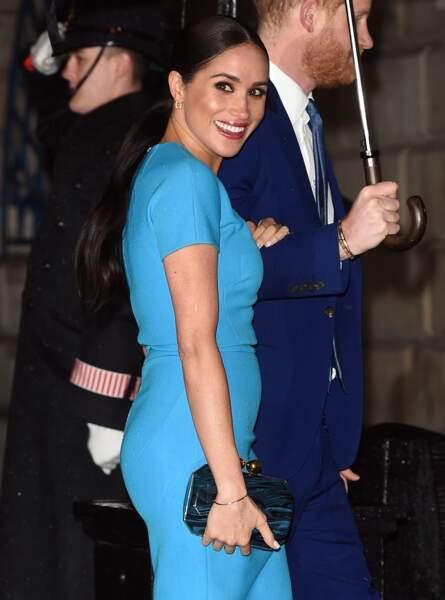 Meghan Markle porte une robe bleue turquoise créée par son amie Victoria Beckham.