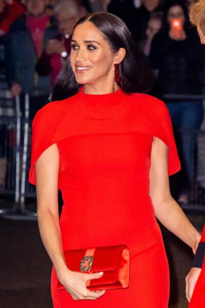 Robe-cape rouge Safyiaa, pochette Manolo Blahnik, boucles d'oreilles Simone Rocha et brushing lisse, Meghan Markle dans l'une de ses plus belles apparitions en tant que duchesse de Sussex.