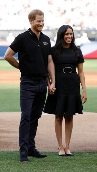 Meghan Markle et le prince Harry en total look black alors qu'ils saluent les équipes de baseball dans le cadre des Invictus Games 2019 au London Stadium, le 29 juin 2019.