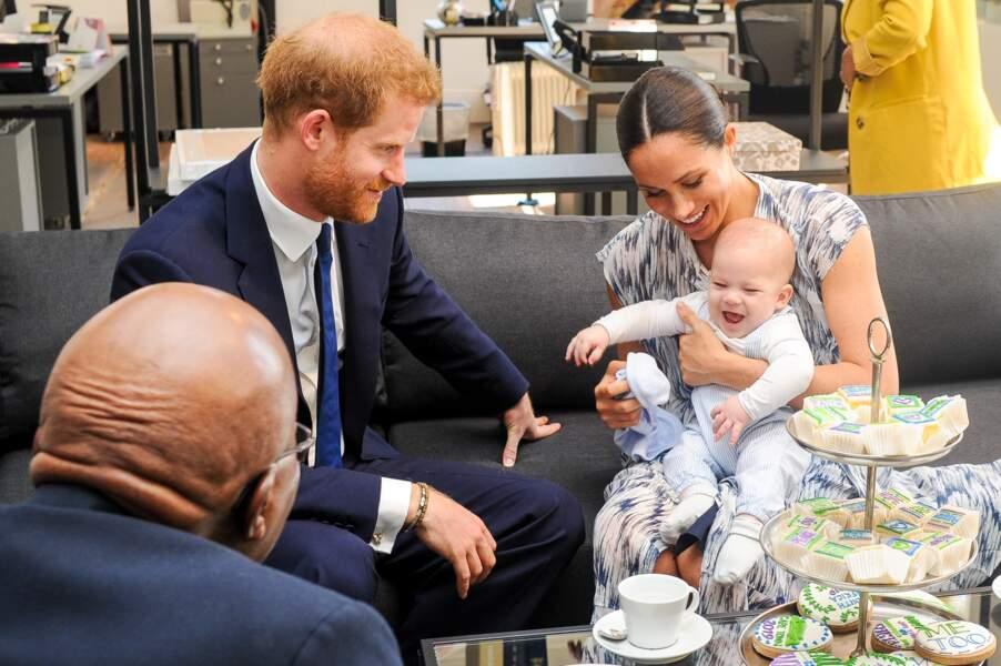Le 25 septembre 2019, Meghan Markle porte une longue robe blanche tachetée de bleu, une robe qui va bien avec la salopette bleue rayée d'Archie et le beau costume bleu marine du prince Harry.