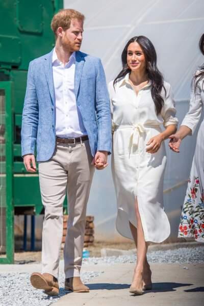 """Le 2 octobre 2019, le prince Harry et Meghan Markle se sont accordés sur des couleurs claires et optent tous les deux pour des chaussures beige-marron en daim pour visiter l'association """"Yes"""" en Afrique du Sud."""