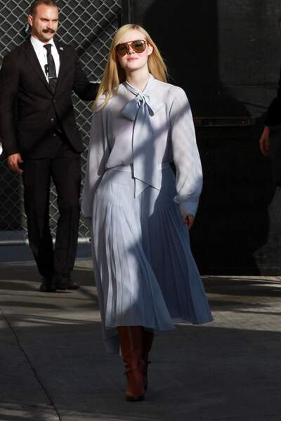 Elle Fanning en chemise à col lavallière bleu pastel et lunettes rétro.