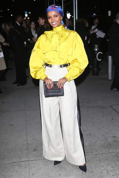 Halima Aden ose la blouse à lavallière en satin jaune.