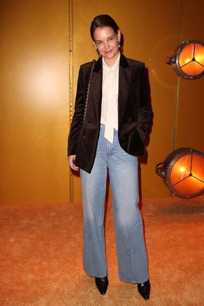 Katie Holmes twiste son jean flare avec une blouse à col lavallière et une veste en velours.