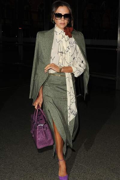 Victoria Beckham cultive l'allure de working-girl avec sa jupe fendue et sa chemise à lavallière à l'imprimé géométrique.