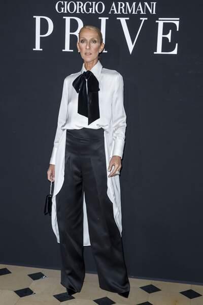 Céline Dion revisite le smoking avec une chemise asymétrique à lavallière contrastée.