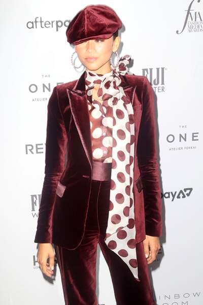 Zendaya twiste son tailleur en velours couleur rouille avec une chemise à lavallière imprimée de pois.