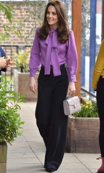 Kate Middleton associe une chemise à lavallière couleur parme à son pantalon de tailleur évasé.