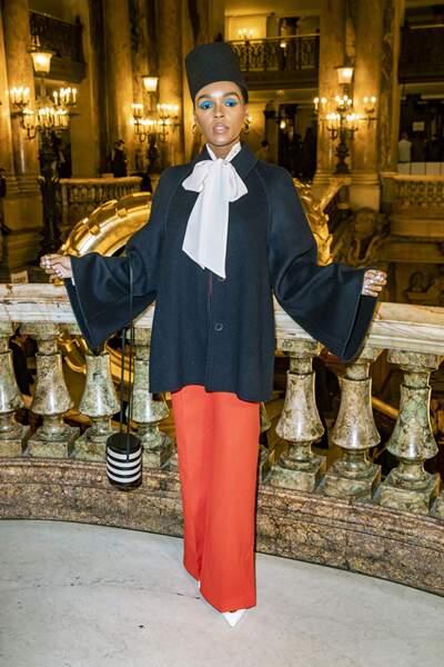 Janelle Monae opte pour une lavallière blanche portée sur un paletot bleu marine et un pantalon corail.