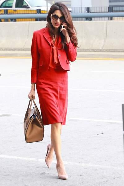 Amal Clooney mixe son tailleur jupe rouge avec une chemise à lavallière orange sanguine.