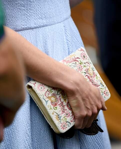 Kate Middleton assortit sa robe bleu  pastel d'une pochette colorée très printanière.