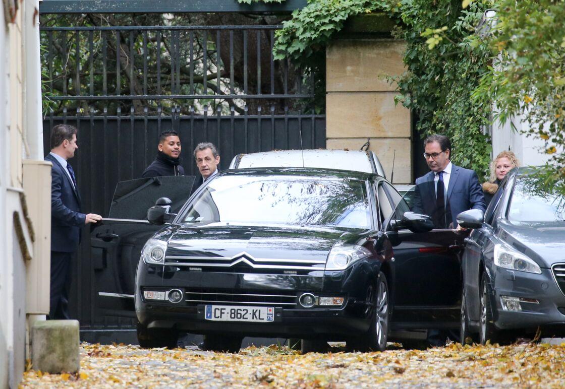 Nicolas Sarkozy, entourés de ses gardes du corps, sortant de son domicile du XVIe arrondissement de Paris.
