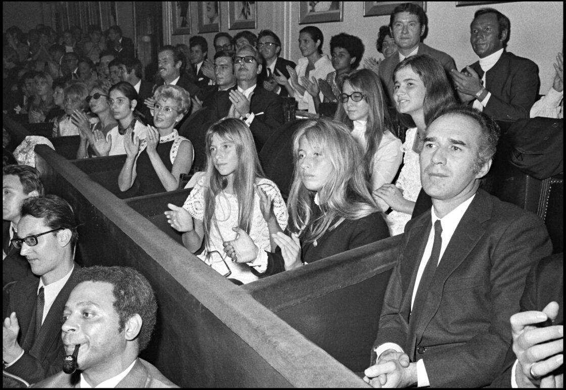 Michel Piccoli assiste à un concert de celle qui est son épouse, Juliette Gréco. Derrière lui, se trouvent Laurence, la fille de Juliette Gréco  et sa fille Anne-Cordélia.