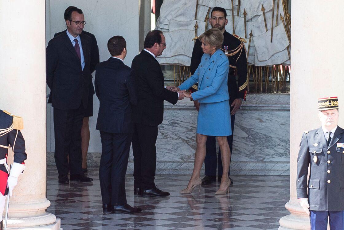 Brigitte Macron saluant François Hollande à distance des photographes, lors de la passation des pouvoirs le 14 mai 2017.
