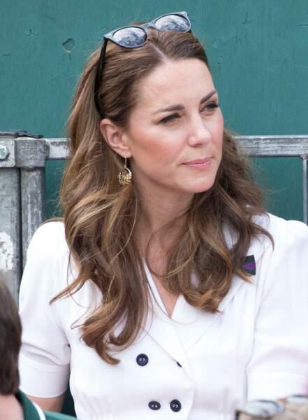 Kate Middleton stylée avec avec ses cheveux longs et ondulés retenus par ses lunettes de soleil à Wimbledon le 2 juillet 2019.