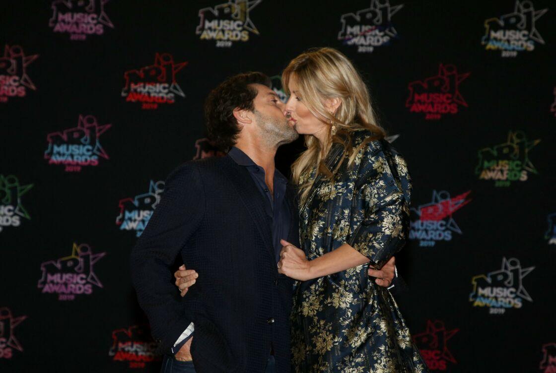 Frédéric Diefenthal et sa compagne Stéphanie s'embrassent sur le photocall des NRJ Music Awards le 9 novembre 2019