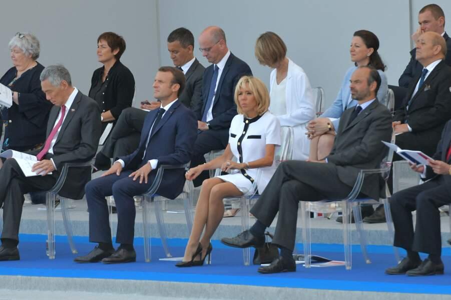 Pour ce 14 juillet 2018, Brigitte Macron avait opté pour une robe blanche et une veste à manches courtes gansée de noir et ornée de boutons dorés, le tout signé Louis Vuitton.