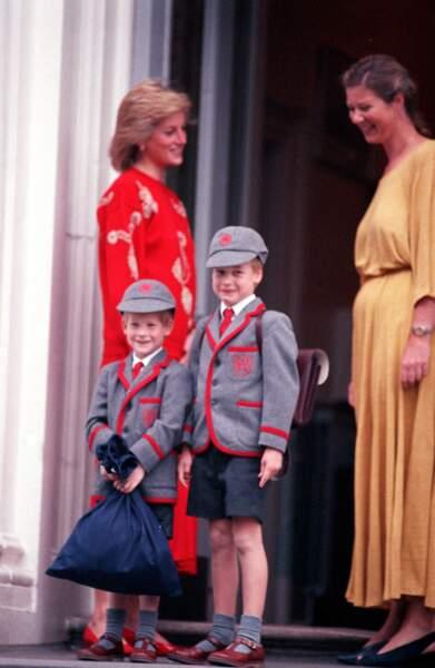 Vêtus de leurs uniformes, cartable sur le dos, William et Harry vont à l'école dans les années 1990. L'aîné veille sur son petit frère.