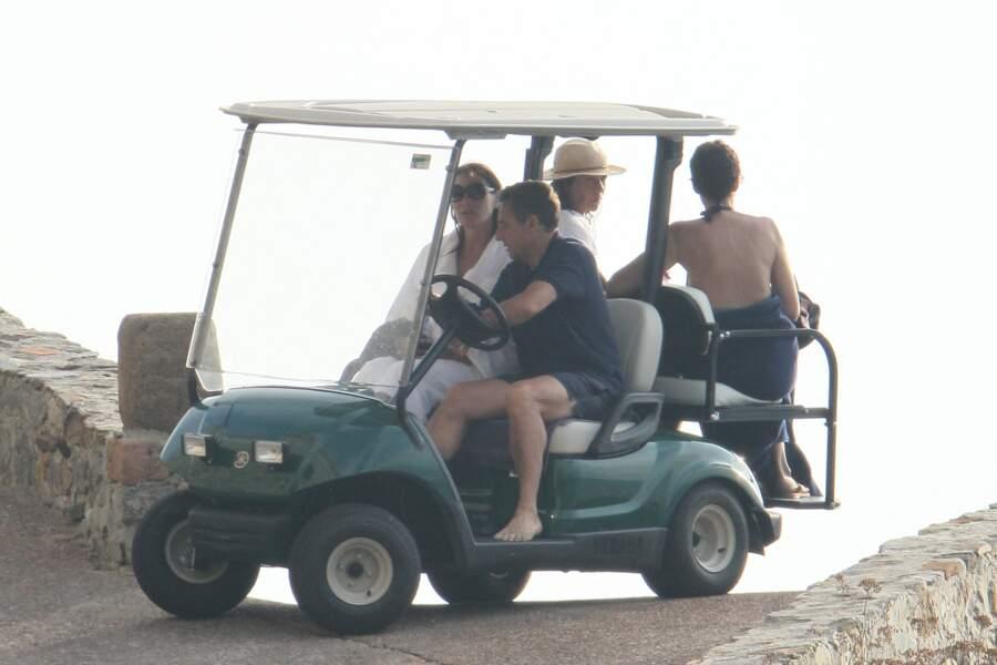 Autre ambiance quand Nicolas Sarkozy et sa femme Carla Bruni débarquent au Fort de Brégançon. Rares apparitions du couple qui se fait discret, comme ici lorsqu'il remonte de baignade en voiturette.