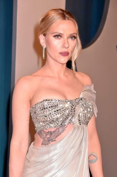 Scarlett Johansson dévoile son tatouage juste sous la poitrine avec cette robe déstructurée.