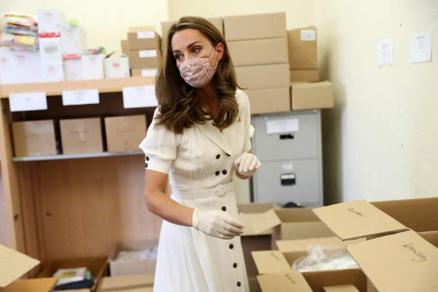 En prenant les précautions nécessaires, Kate Middleton aide les bénévoles ce mardi 4 août