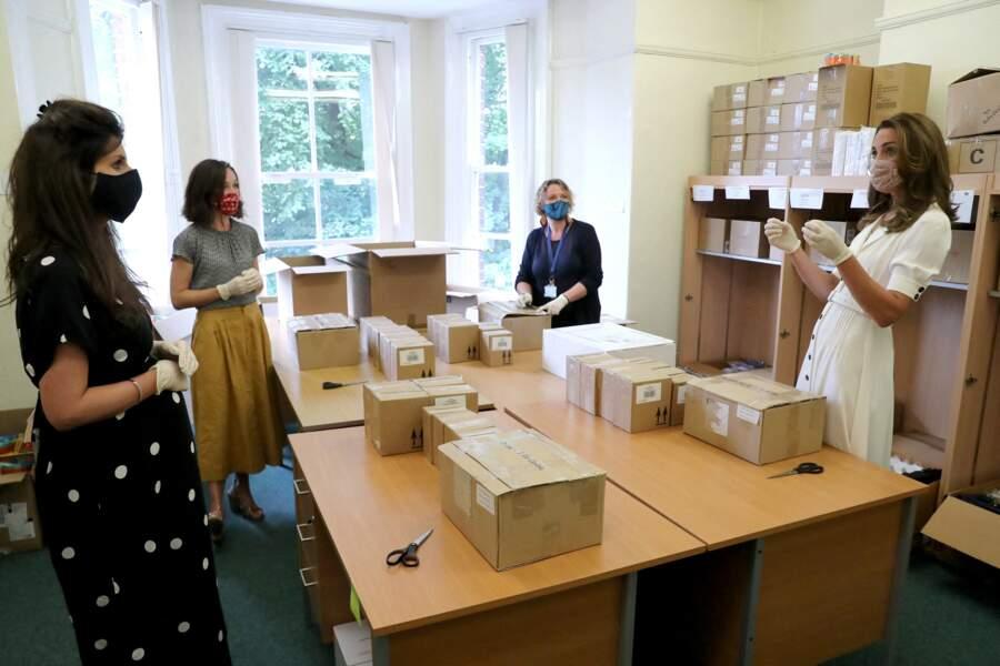 Kate Middleton, masquée et gantée, discute avec des bénévoles en déballant des cartons de dons, ce mardi 4 août