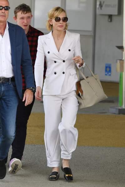 Cate Blanchett opte pour un style tailleur décontracté lors de son arrivée au Festival de Venise en 2018. Elle porte une veste blanche boutonnée qu'elle associe à un pantalon blanc large et une paire de mules noires.