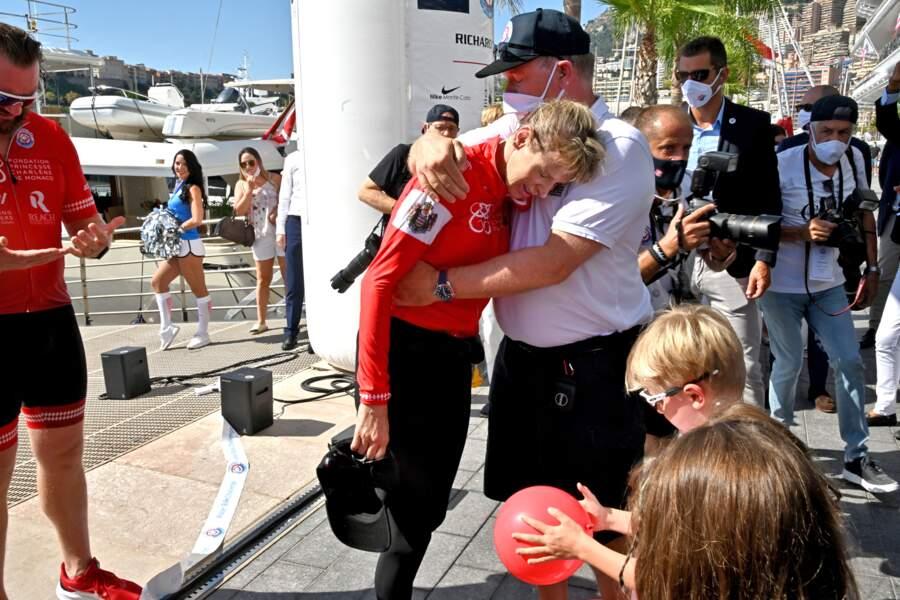 """Le prince Albert II de Monaco enlace sa femme la princesse Charlène, qui a franchi la ligne d'arrivée de la course """"The Crossing : Calvi-Monaco Water Bike Challenge""""."""