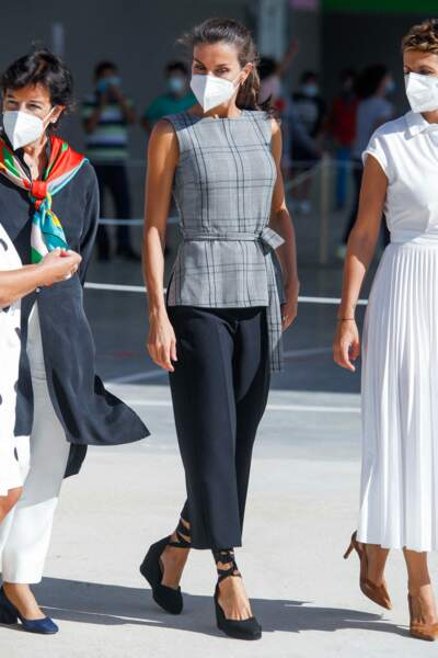 La reine d'Espagne portait un pantalon ample noir sept huitième et un haut prince de Galles ceinturé gris.