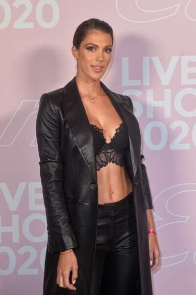 Pour assister au défilé Etam Live Show 2020, Iris Mittenaere portait un long pantalon en cuir évasé de la marque Jitrois Paris et un long trench en cuir noir.