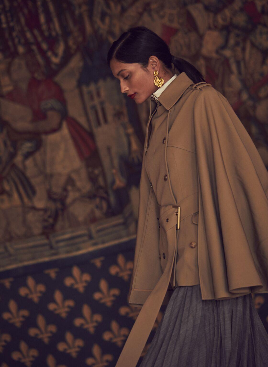 Cape trench en gabardine de laine, col roulé en viscose et jupe plissée en laine, le tout Michael Kors Collection. Boucles d'oreilles en métal Escada.