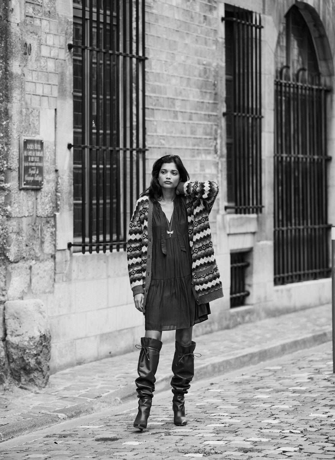 Gilet en laine mélangée La Petite Française, robe Caroll. Collier Thomas Sabo, bottes Tory Burch.