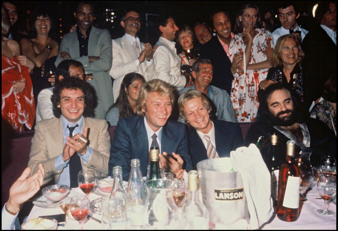 Claude François et Johnny Hallyday, tout sourire lors d'une soirée parisienne, aux côtés de Michel Sardou et Demis Roussos.