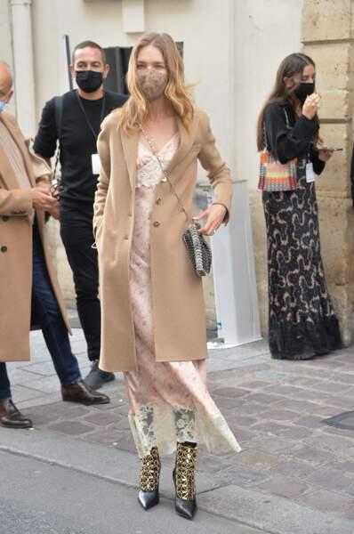 Natalia Vodianova au défilé Paco Rabanne collection Printemps-Eté 2021 a associé robe dentelle, manteau camel et bottines rock.