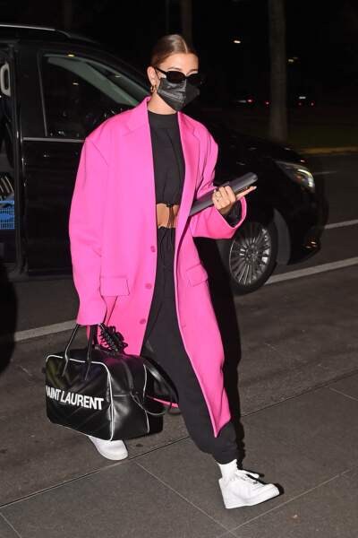 Hailey Baldwin Bieber illumine son look street avec un long manteau rose flashy.