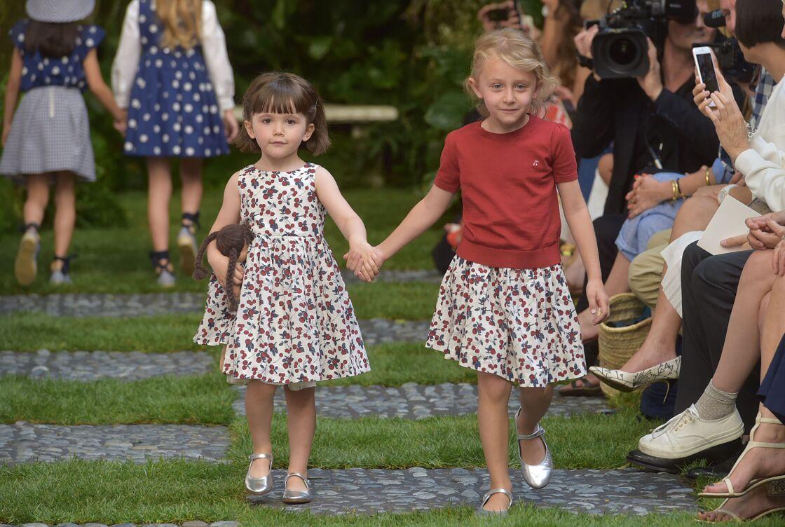 Esther Testud, la fille de Sylvie Testud (à droite), défile tout sourire pour la marque pour enfants Bonpoint, lors de la Fashion Week parisienne de juillet 2016.