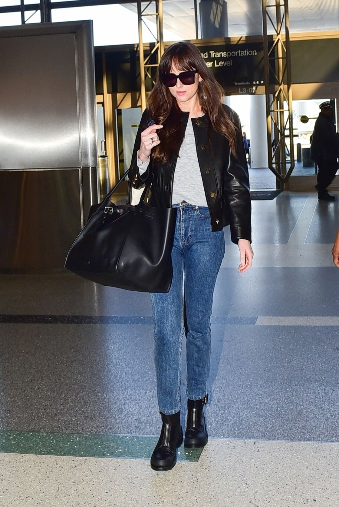 Dakota Johnson affiche un look casual pour voyager : veste en cuir, jean et bottines.