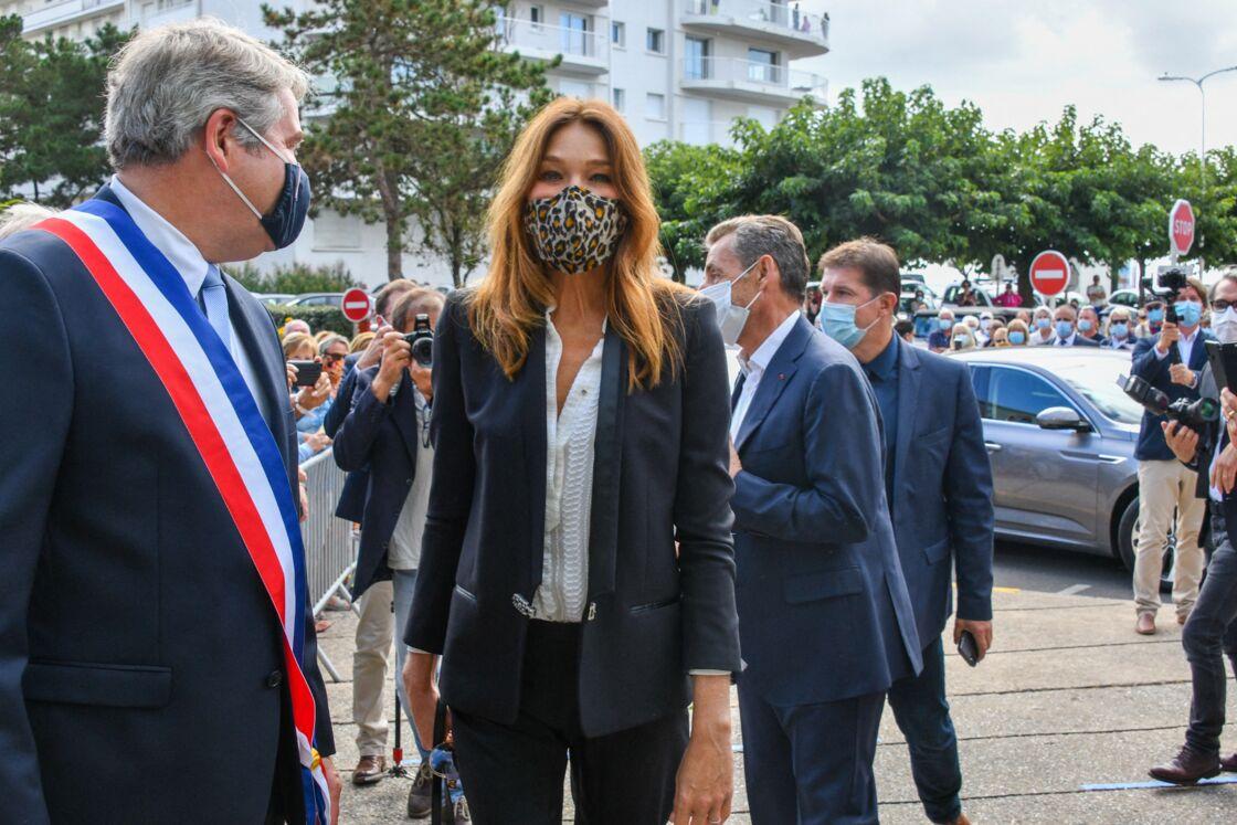 Carla Bruni arbore un masque imprimé léopard à l'occasion d'un mariage.