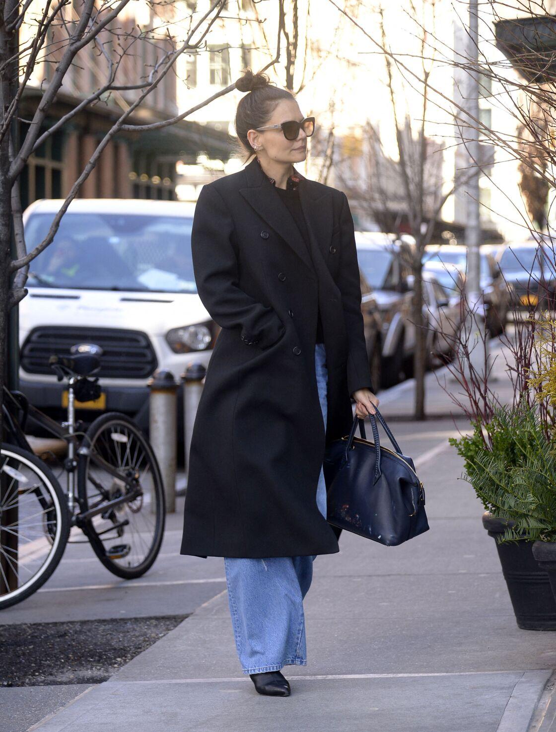 Katie Holmes flâne dans les rues de New York en jean flare et manteau long.