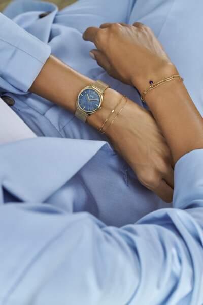 Le cadran en perle bleue de la collaboration Cluse x Iris Mittenaere est associé à un boitier doré et un bracelet en maille milanaise assorti pour un effet chic et éclatant