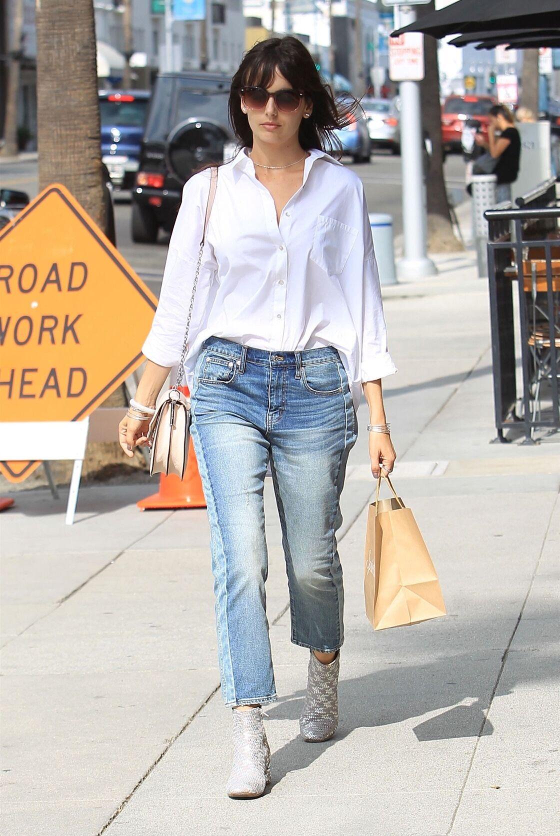 Camilla Belle porte à merveille le look casual en chemise blanche avec un jean bleu délavé bootcut et une paire de bottines argentées
